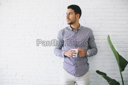 young businessman standing against wall holding