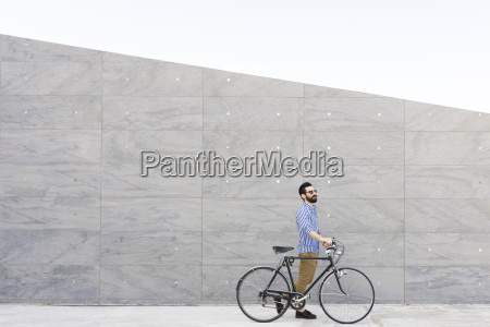 young man with bicycle in front