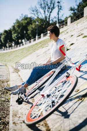 young woman with bicycle sitting on