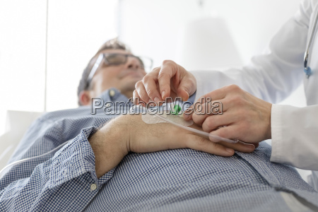 doctor applying infusion to patients hand