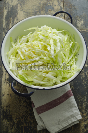 chinese cabbage in sieve on wood