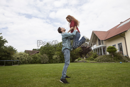 happy man lifting up woman in