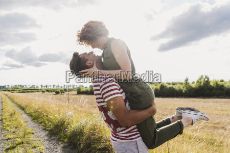 happy young man lifting up girlfriend