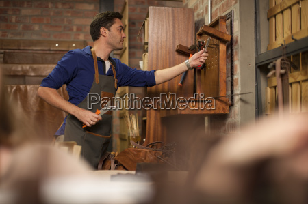 man hanging up tools in workshop