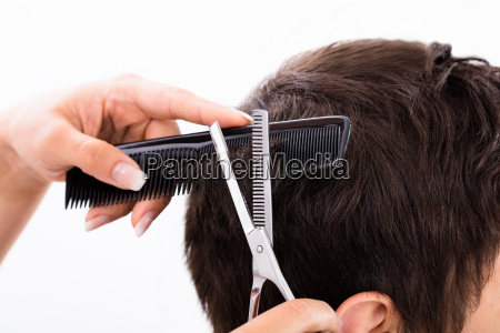person getting haircut from hairdresser