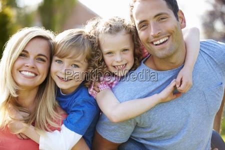 parents giving children piggyback rides in
