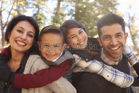 portrait of happy parents piggybacking kids