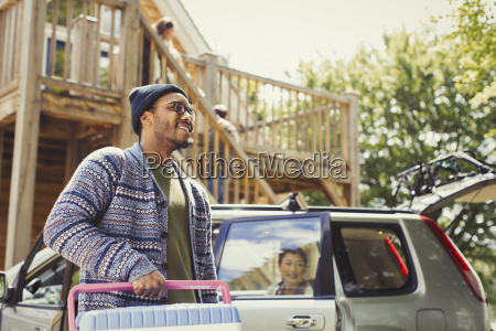 smiling man carrying cooler outside car