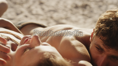 young couple sunbathing on sunny beach