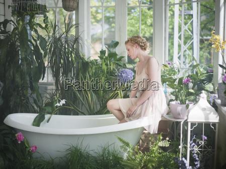 junge frauam rand der badewanne im