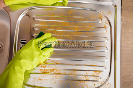 woman cleaning untidy stainless steel sink