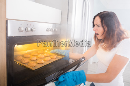 woman looking at burnt cookies near