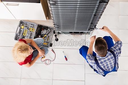 male worker repairing refrigerator in kitchen