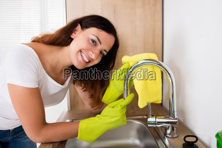 happy woman cleaning the tap