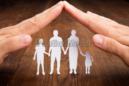 person hand protecting family papercut