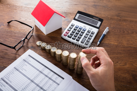 person stacking coins on wooden desk