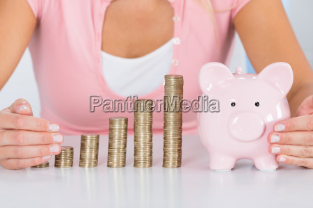woman protecting piggybank with stack of