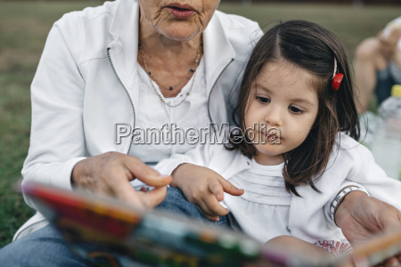 grandmother showing picture book to granddaughter