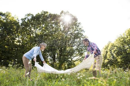 senior couple spreading out blanket on