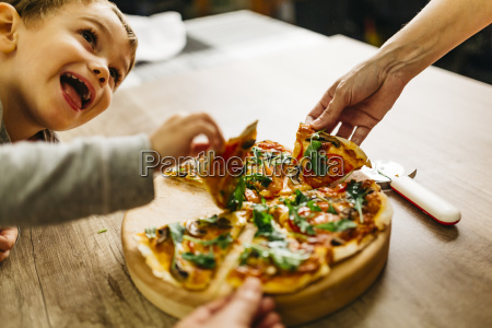 father and son picking up pizza