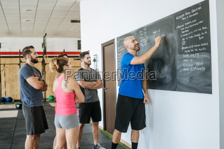 coach in a fitness class writing