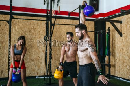 group of athletes lifting kettlebells in