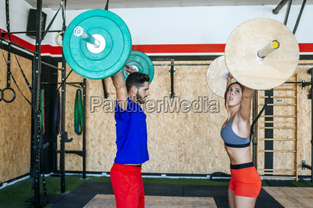 man and woman lifting barbells in
