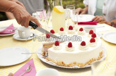 hand cutting cream cake