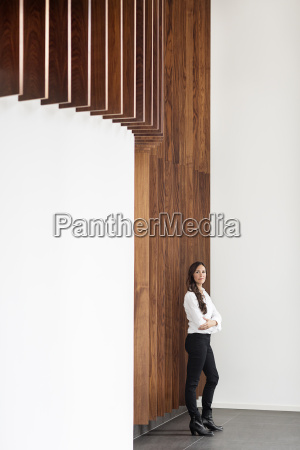 confident businesswoman standing at wooden wall