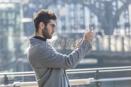 young businessman taking picture with smartphone