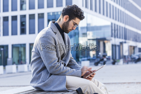 young man sitting on bench using