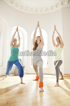 three women in sunny yoga studio