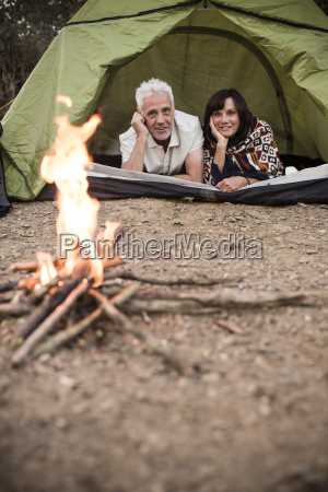 happy senior couple lying in tent