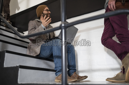 hip creative professional sitting on stairs
