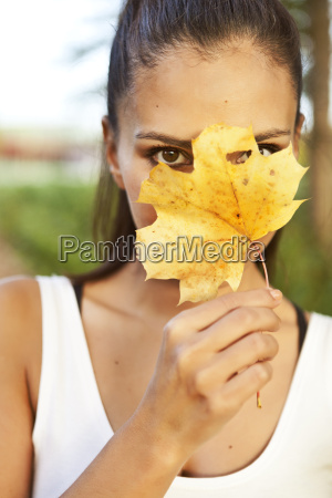 woman holding up an autumn leaf