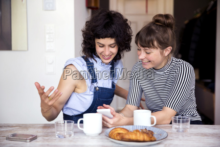 two women at breakfast table looking