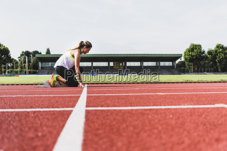 young woman on tartan track in