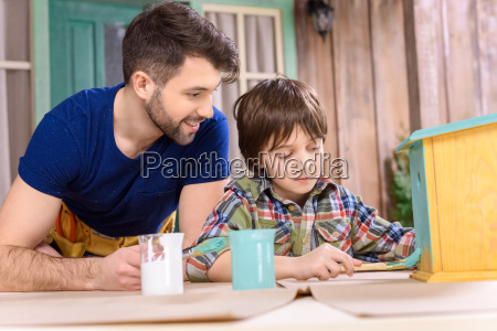 happy father looking at concentrated little