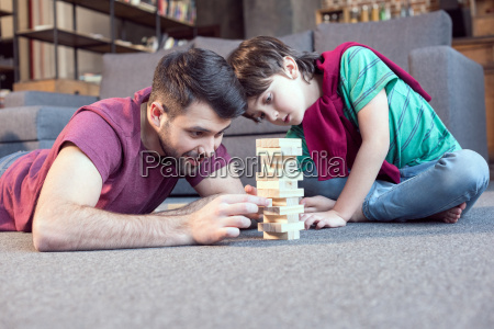 smiling father and focused son playing