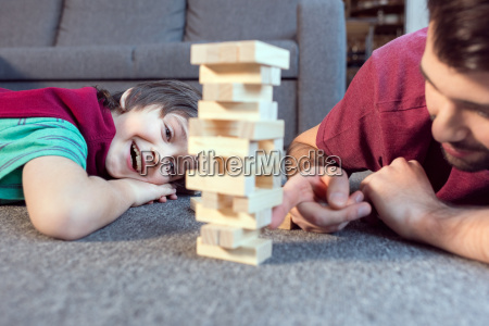cheerful son and father playing jenga