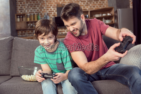 cheerful father and son playing video