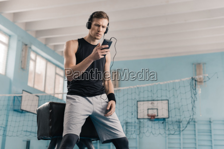 athletic young man in headphones with