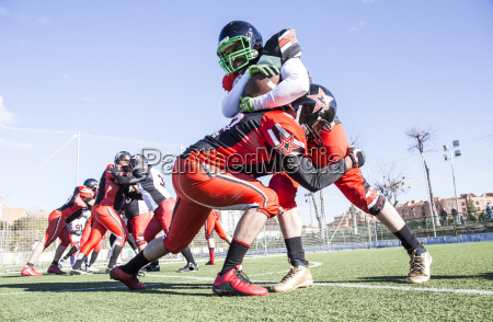 american football player being tackled by