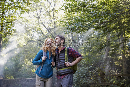 couple hiking in forest looking up