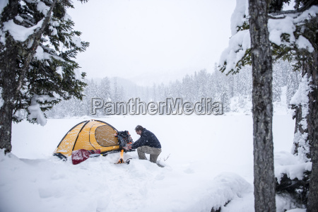 senior man camping in snow covered