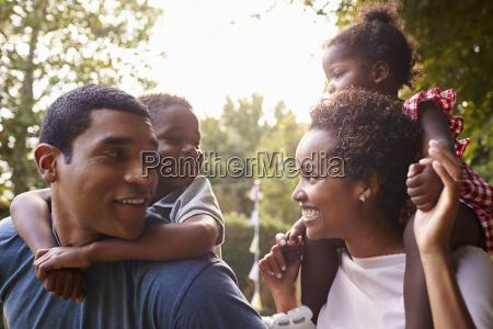 african american parents giving children piggyback