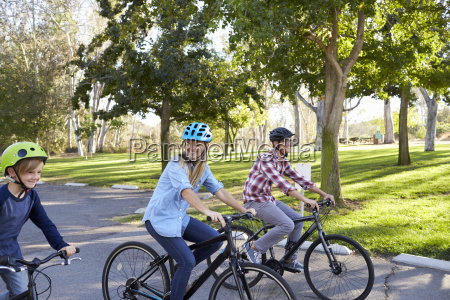 parents and young son cycling through