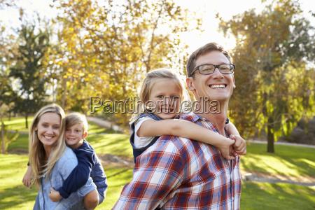 parents carry kids piggyback in park
