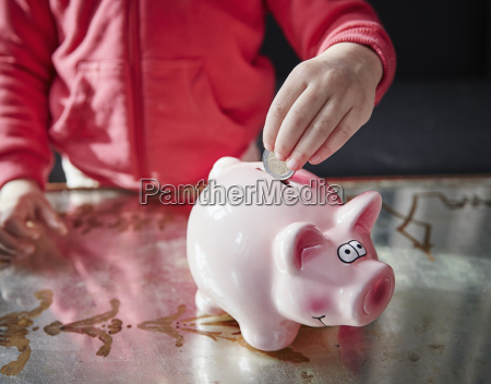 girl putting coin into piggy bank
