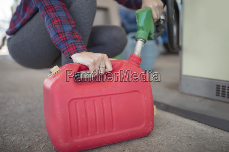 woman filling up canister at fuel